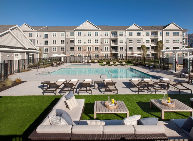 View of Pool Area, Showing Loungers, Outdoor Couches, and Apartment Building in the Background at Parc Westborough Apartments